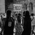 Black and white image of a woman holding a sign that says 'ENOUGH'
